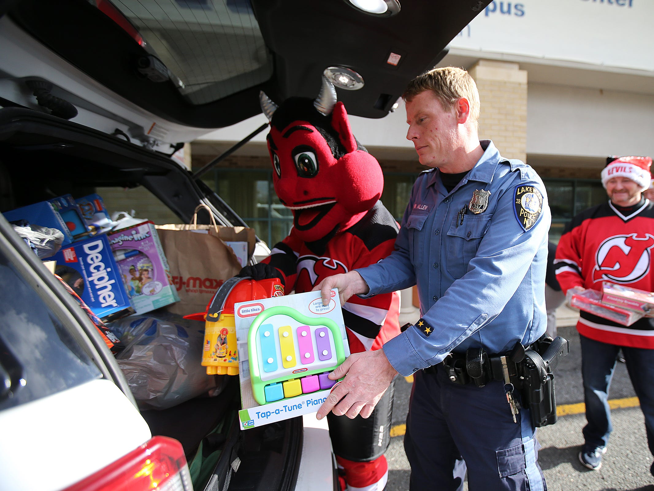 The New Jersey Devils' mascot and Lakewood Police Officer William Allen pack donated toys into a police car during a visit to the Monmouth Medical Center Southern Campus in Lakewood, NJ Monday, December 17, 2018.