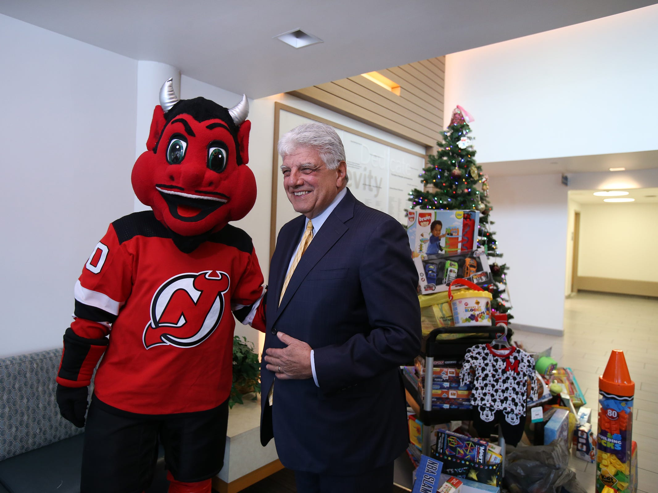 The New Jersey Devils' mascot greets Dr. Frank Vozos, president and CEO of Monmouth Medical Center Southern Campus, during a visit to the Monmouth Medical Center Southern Campus in Lakewood, NJ Monday, December 17, 2018. During his visit, he loaded donated toys into a police car with members of the Lakewood PBA and Lakewood Police Department.