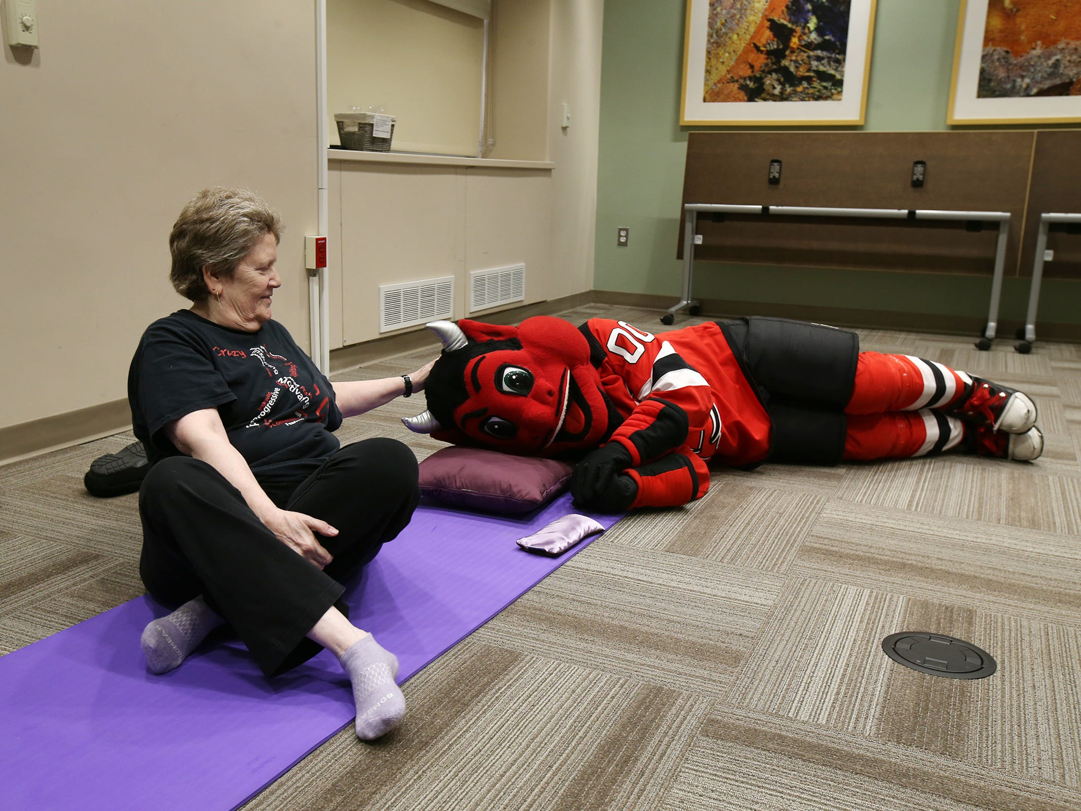 The New Jersey Devils' mascot visits Rachel Halfant of Toms River during her meditation class during a visit to the Monmouth Medical Center Southern Campus in Lakewood, NJ Monday, December 17, 2018. During his visit, he also loaded donated toys into a police car with members of the Lakewood PBA and Lakewood Police Department.