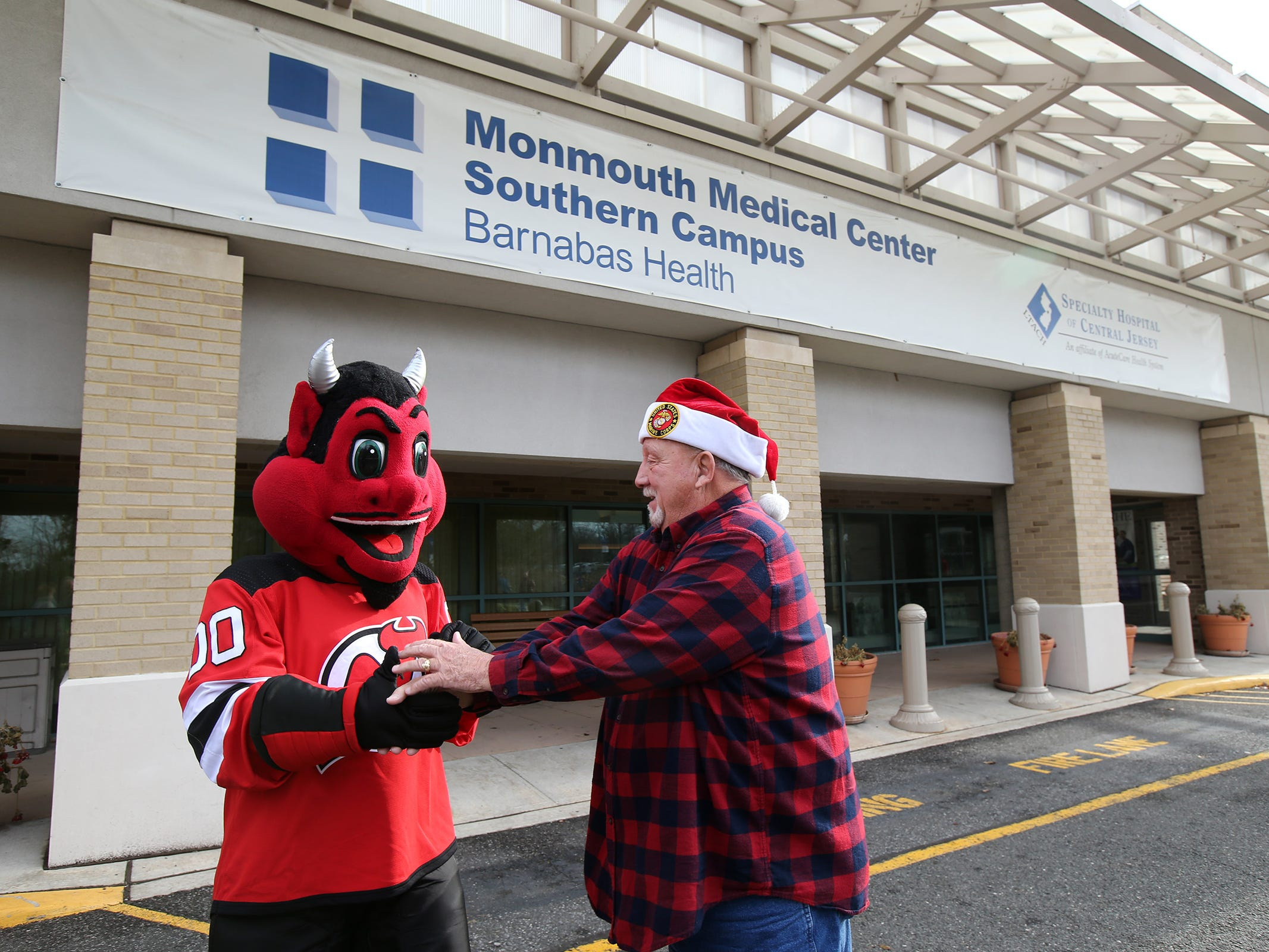 The New Jersey Devils' mascot greets Ed Ward of Lakewood, a retired Lakewood police detective, at the Monmouth Medical Center Southern Campus in Lakewood, NJ Monday, December 17, 2018. During his visit, he loaded donated toys into a police car with members of the Lakewood PBA and Lakewood Police Department.