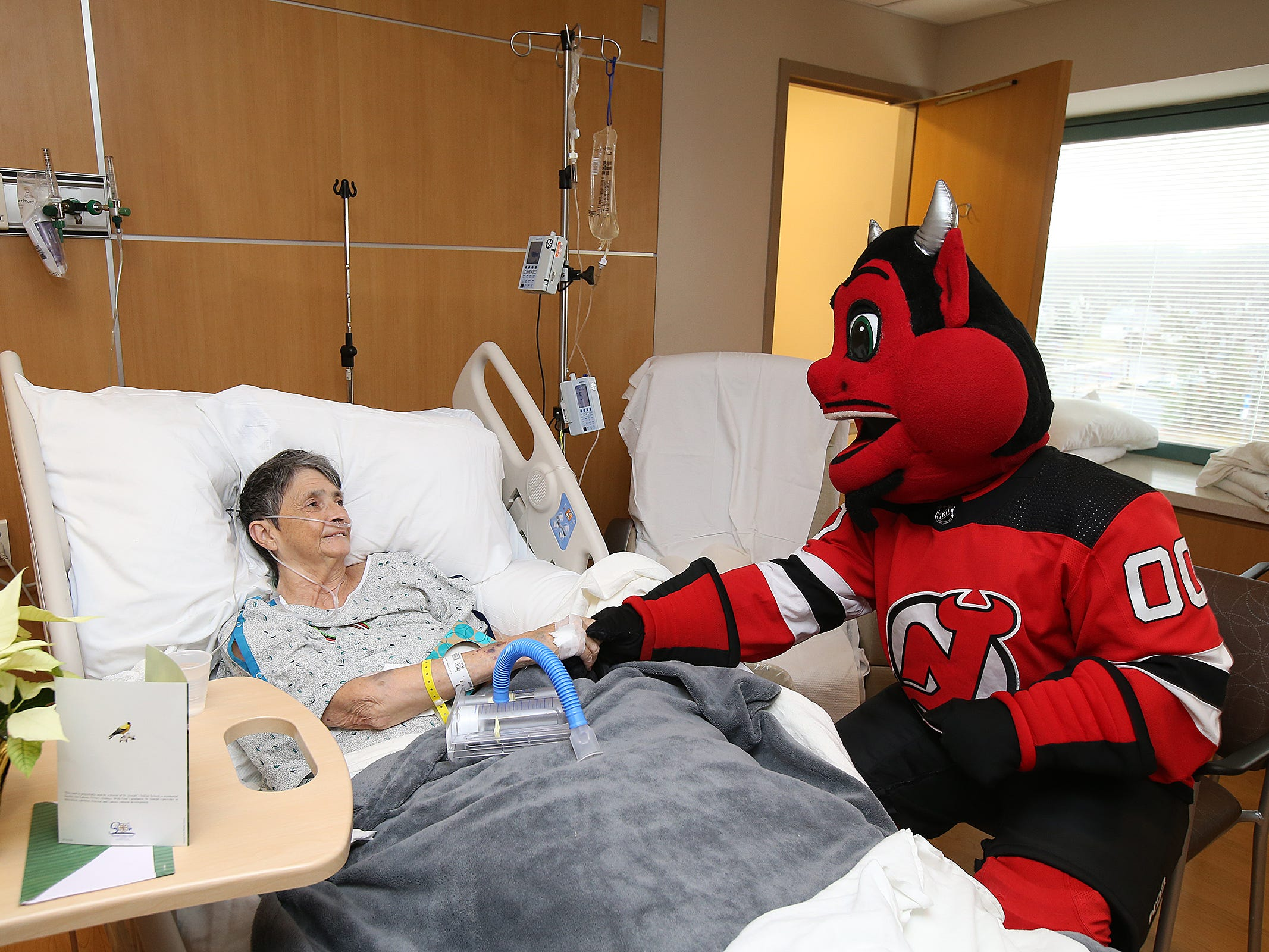 The New Jersey Devils' mascot visits Mary Layton of Lakewood in her hospital room during a visit to the Monmouth Medical Center Southern Campus in Lakewood, NJ Monday, December 17, 2018. During his visit, he also loaded donated toys into a police car with members of the Lakewood PBA and Lakewood Police Department.