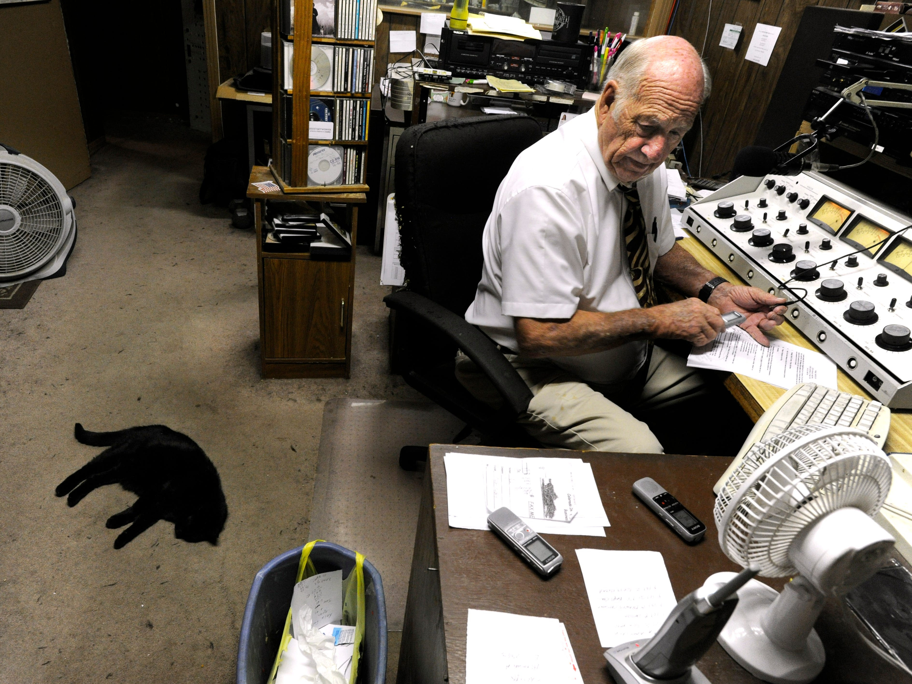 Jim Baum searches through his audio recorders for the evening's Colorado City Council meeting Tuesday June 11, 2013. Baum is the mayor and owner of KVMC/KAUM radio. After each meeting, Baum returns to the station to edit together a report for the next morning's newscast.