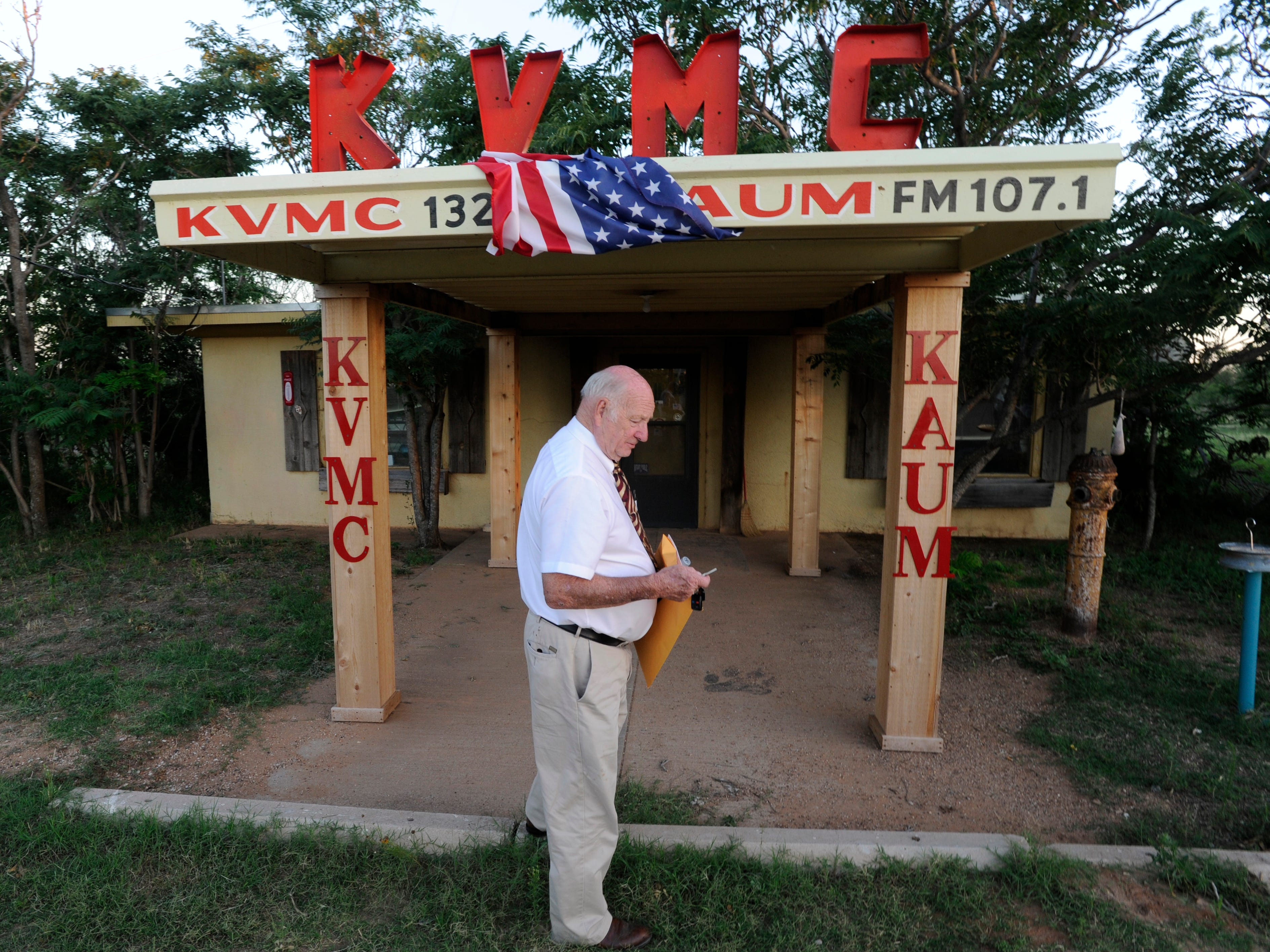 Jim Baum checks his keys before entering his radio station, the American flag having blown by the wind between the call letters, Tuesday June 11, 2013. Baum is the owner of KVMC/KAUM radio and the mayor of Colorado City.