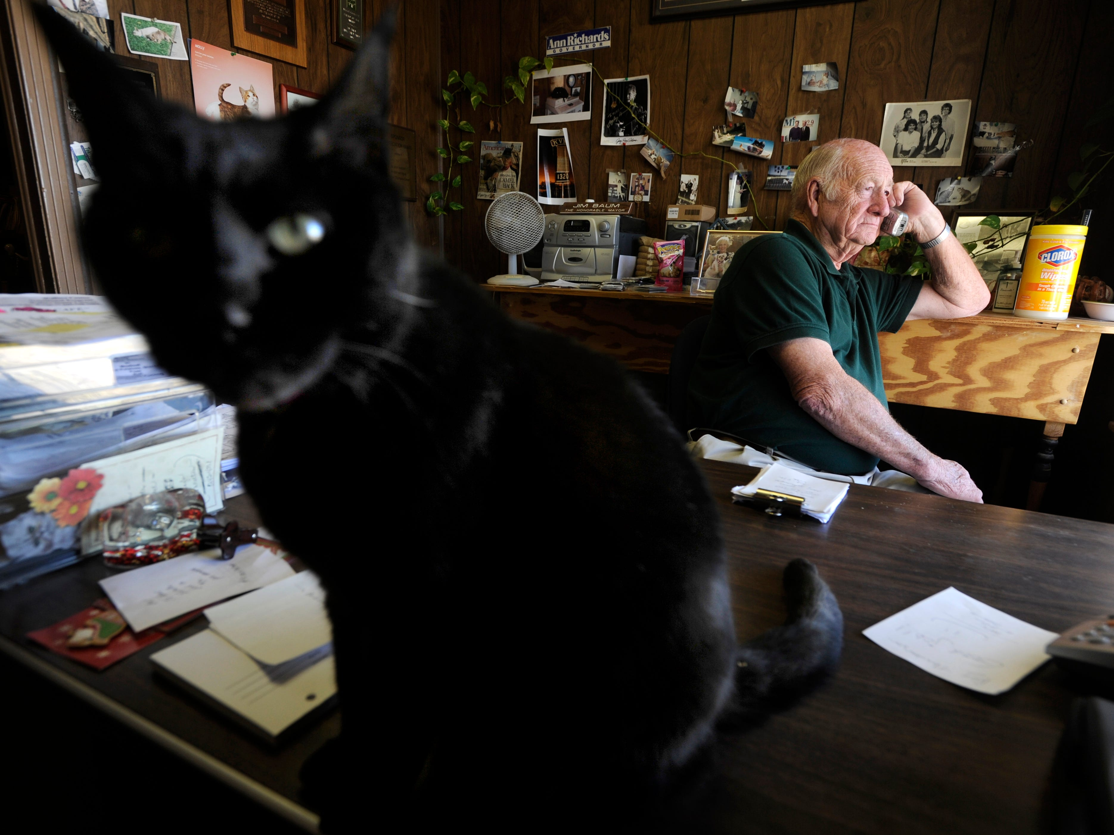 Squeak, the station cat at KVMC/KAUM in Colorado City, sits on the edge of Jim Baum's desk as he fields a call Monday, Feb. 28, 2011. People were calling in to express their thanks to Baum for keeping them informed during the previous night's wildfire that destroyed several homes north of town. Baum, who bought the station in 1980, died Sunday Dec. 16, 2018.