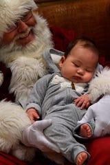 Four-month-old Ryusuke Thaxton dozes in Santa Claus' lap at the Abilene Zoo.