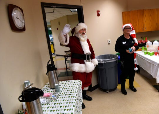 Santa Claus enters the room at the Abilene Zoo for breakfast with youngsters.