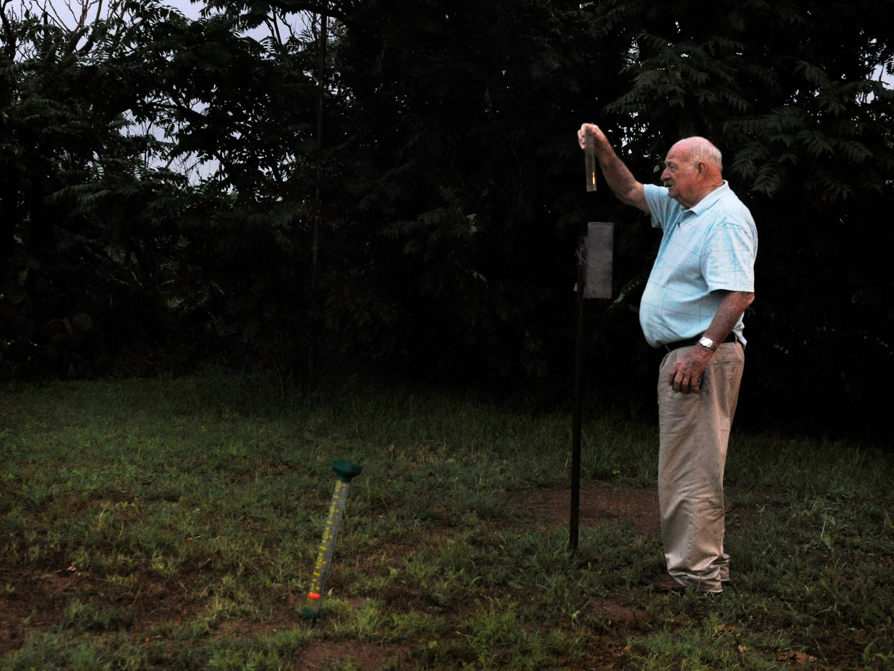 Jim Baum, the owner of KVMC/KAUM radio and the mayor of Colorado City, takes a measure of one of his rain gauges Thursday evening May 28, 2015 outside of the station. Baum has been keeping daily weather measurements at the station since 1982.