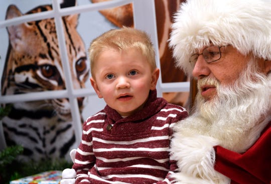 Austin Cox, 2, sits on Santa Claus' knee in December 2018 at the Abilene Zoo.