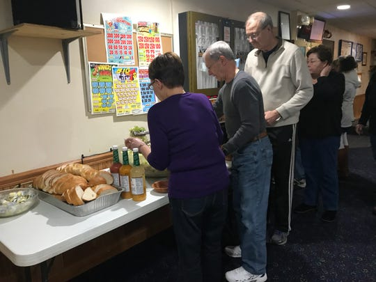 Attendees of the Endicott Sons of Italy's Friday lunch on Nov. 30 help themselves to Italian bread and salad.