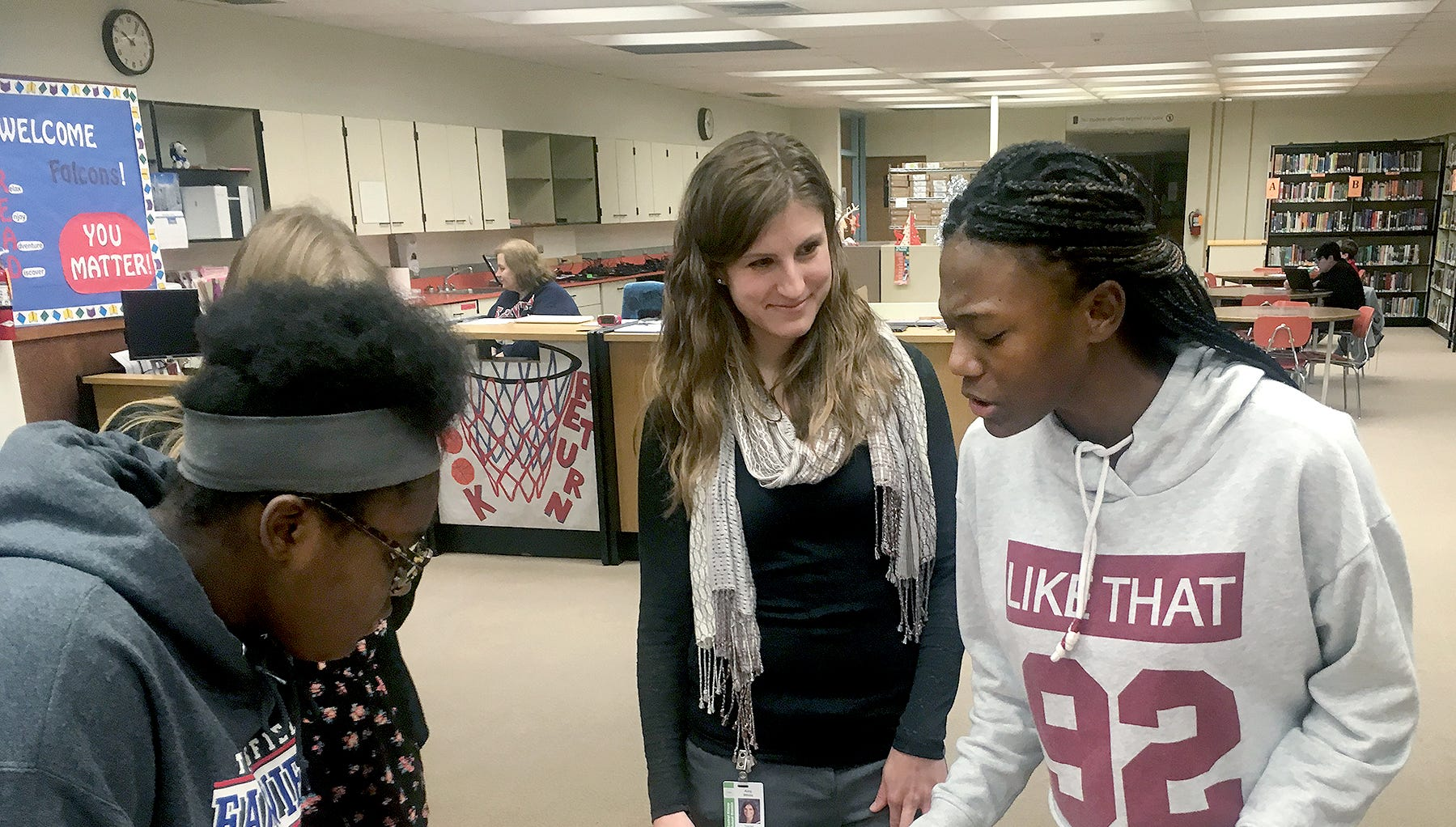 Fairview Middle School student N'Dya Hudson explains to her teacher Amy White the images in her artwork for a project in White's U.S. History class, focused on the history of racial discrimination. Listening is her fellow student Kaleah Riley.