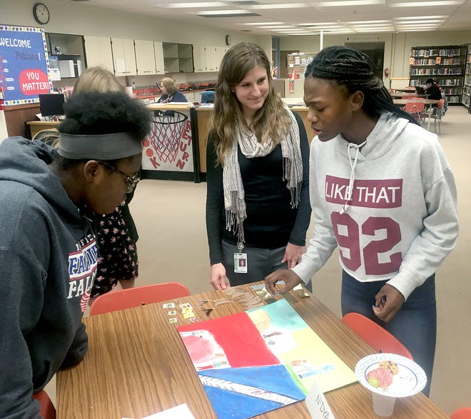 Fairview Middle School student N'Dya Hudson explains to her teacher, Amy White, the images in her artwork for a project in White's U.S. history class, focused on the history of racial discrimination. Listening is her fellow student Kaleah Riley.
