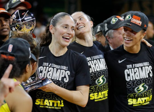 Storm guard Sue Bird, left, holds the WNBA championship trophy on Sept. 18, after she led Seattle to a sweep of the Washington Mystics.
