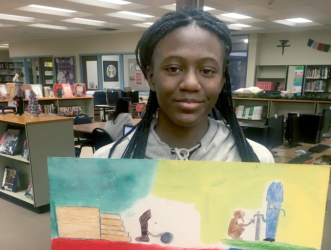 "Fairview Middle School student N'Dya Hudson displays her artwork for a project in Amy White's U.S. History class, focused on the history of racial discrimination. A ""ladder to success"" on the bottom right shows a white person cutting before a black person."