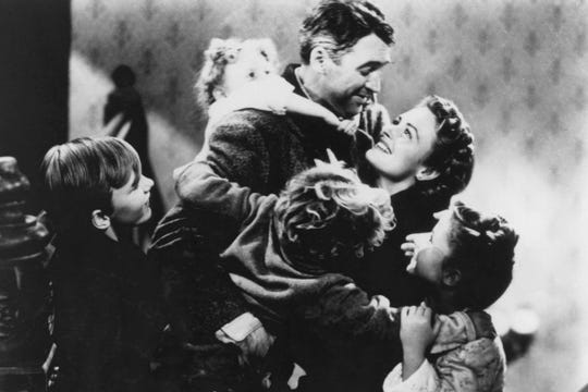"George Bailey (Jimmy Stewart) and his wife Mary (Donna Reed) celebrate with their children in ""It's a Wonderful Life."""