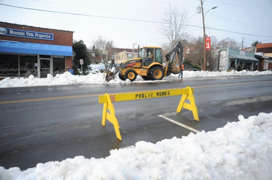 Public services crews clear snow off of parking spaces in downtown Black Mountain on Dec. 13.