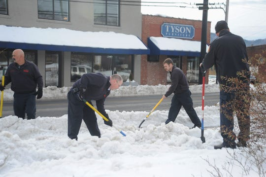 Black Mountain firefighters shovel snow off the sidewalk along East State Street four days after a winter storm dumped over a foot-and-a-half of snow on the Swannanoa Valley.