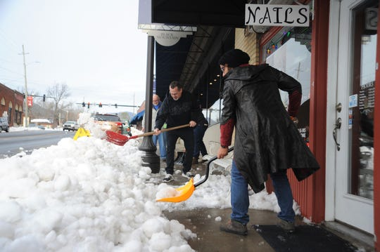 Tyson Furniture Co. employees shovel snow off the sidewalk on the east side of Broadway Avenue on Dec. 13.