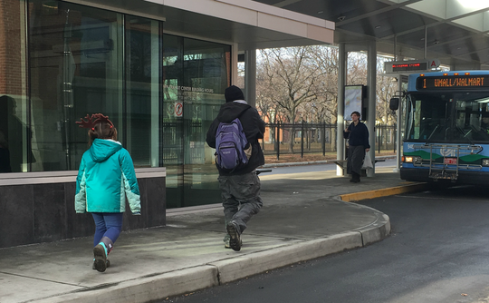 Pedestrians prepare to catch the Green Mountain Transit #1 bus at the downtown Burlington terminal on Saturday, Dec. 15, 2018.