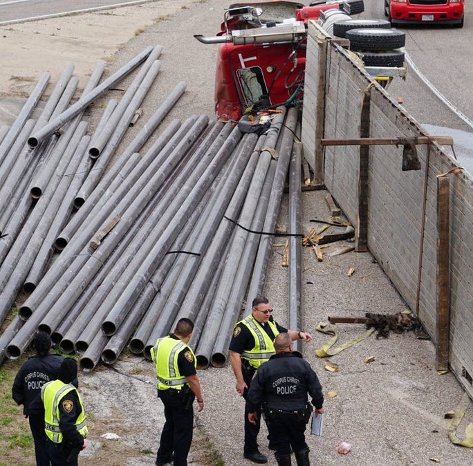 Flatbed trailer rolls over at on-ramp at base of Harbor Bridge