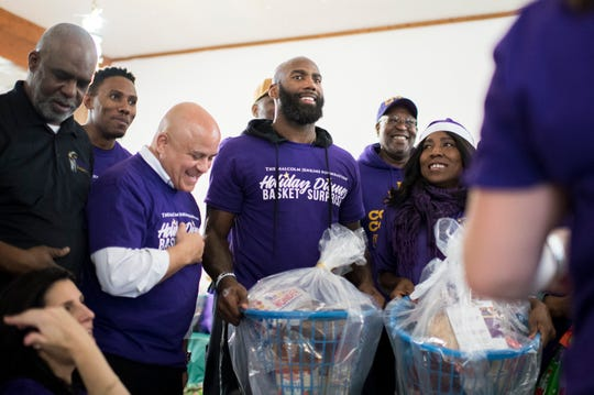 Malcolm Jenkins, center, smiles alongside Camden Mayor Frank Moran, left, and his mother Gwendolyn Jenkins as they pose for photos Monday, Dec. 17, 2018 in Camden, N.J. The Malcolm Jenkins Foundation put together holiday dinner baskets for families in the area.