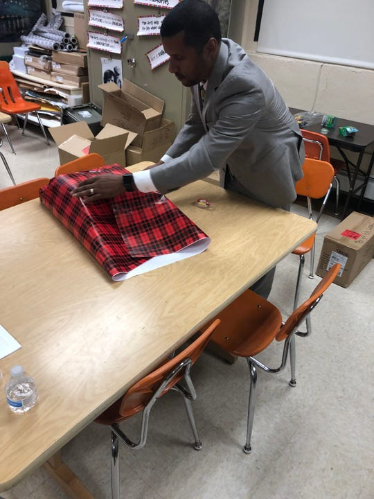 """A Santa Claus of sorts, New Brunswick teacher Jennifer Olawski is ensuring that every single of of her more than 450 students will receive a gift this holiday season. Continuing a program she began in her former school, Olawski, a physical education and health teacher at Livingston Elementary School, created a GoFundMe campaign to raise funds for gifts for the children. This year's effort saw more than $10,000 in donations and the help of many school """"elves,"""" such as Superintendent Dr. Aubrey Johnson, who came to help wrap gifts."""
