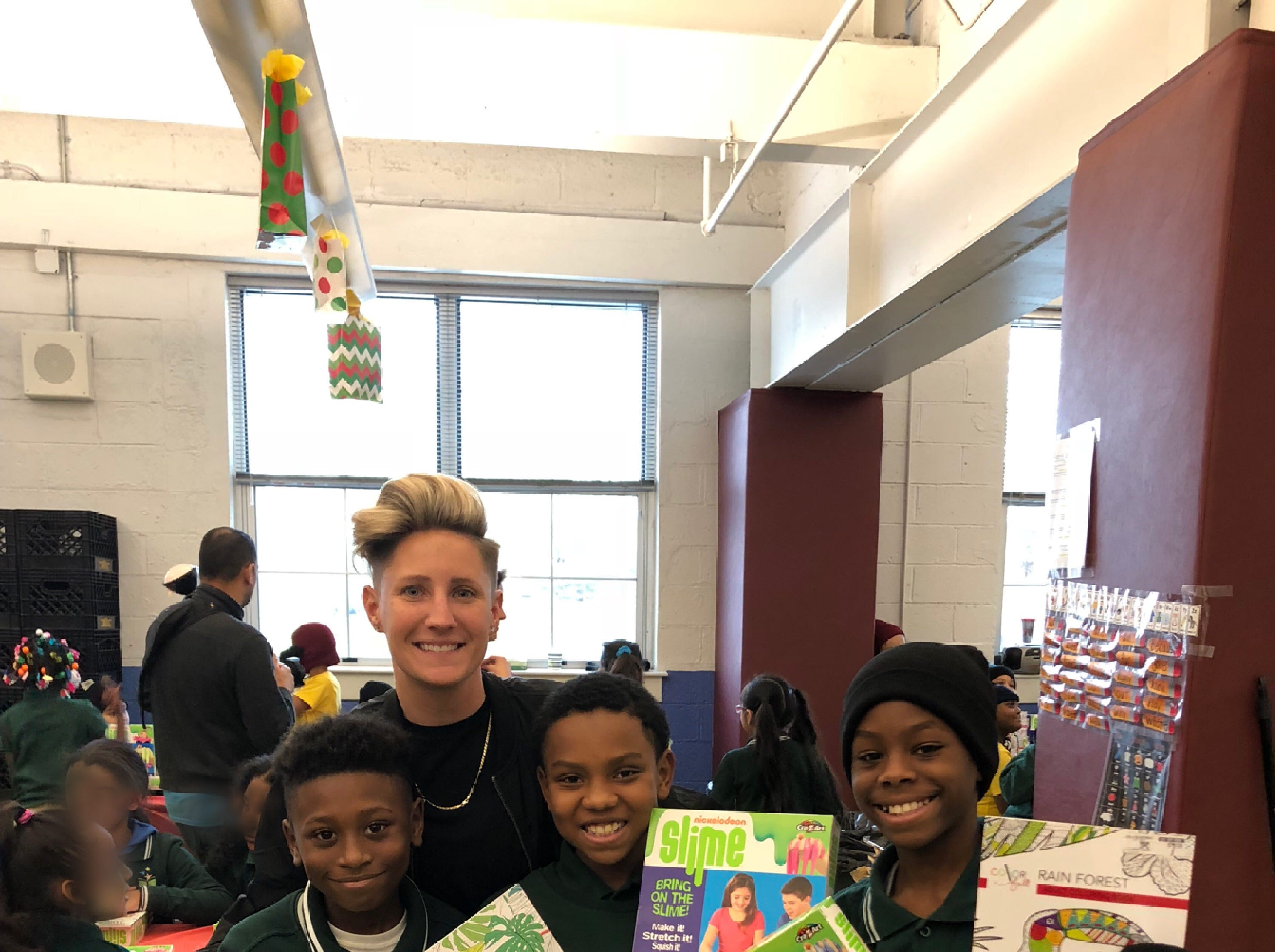 """A Santa Claus of sorts, New Brunswick teacher Jennifer Olawski is ensuring that every single of of her more than 450 students will receive a gift this holiday season. Continuing a program she began in her former school (pictured here with Kyzoir, Jason and Kadir), Olawski, a physical education and health teacher at Livingston Elementary School, created a GoFundMe campaign to raise funds for gifts for the children. This year's effort saw more than $10,000 in donations and the help of many school """"elves."""""""