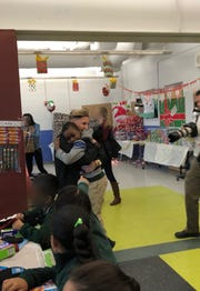 """A Santa Claus of sorts, New Brunswick teacher Jennifer Olawski is ensuring that every single of of her more than 450 students will receive a gift this holiday season. Continuing a program she began in her former school (pictured here with Isaac Morris), Olawski, a physical education and health teacher at Livingston Elementary School, created a GoFundMe campaign to raise funds for gifts for the children. This year's effort saw more than $10,000 in donations and the help of many school """"elves."""""""