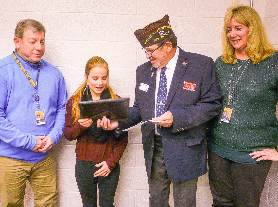 Gerald Cadwallader of the VFW presents Del Val High School sophomore Clare Erwin with a plaque and a check for winning the Hunterdon County Voice of Democracy competition. They are flanked by teacher Jim Kluska and Principal Adrienne Olcott.