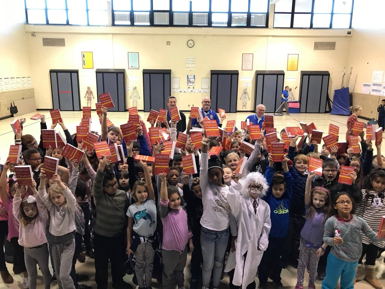 Manville third-graders learn that caring includes community support from service organizations.  The Rotary Club of Hillsborough members (back row) handed out free dictionaries to all third-graders.