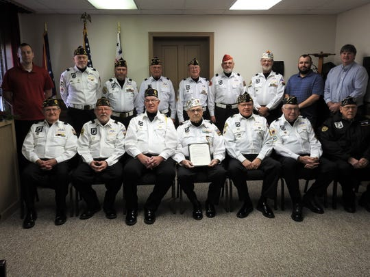 Members of the Coshocton County Honor Guard and Veterans Service Office honor Fred Lent, seated center, for serving in 1,000 military funerals along with a proclamation from Coshocton County Commissioners.