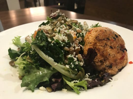 The Citrus Kale Power Salad, topped with a salmon cake at Teddy Maroon's.