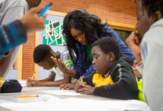 Tricia Gabriel, co-founder of Genesis Youth Foundation works with kids at Moore elementary Thursday, Dec. 6, 2018.