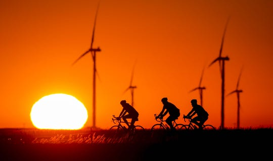 Riders pass the sunrise early morning outside of Grand Junction, Iowa, Tuesday, July 24, 2018, as RAGBRAI 2018 heads to the overnight town of Ames.