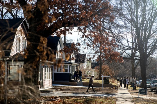 People walk in and out of a pair of houses in the Woodland Heights Neighborhood remolded by Ryan Francois, the creator and owner of Rally Cap Properties, during an open house on Sunday, Dec. 16, 2018, in Des Moines.