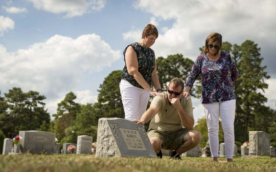 "Children of A.W. ""Dub"" Barron Connie Hoye, left, Wade Mulligan, kneeling, and Lori Stangl at the gravesite of Barron, Saturday, September 1, 2018, in Tyler, Texas. Mulligan was seeing the gravesite of his father for the first time."