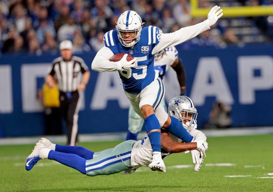 Indianapolis Colts' Eric Ebron runs out of a tackle by Dallas Cowboys' Chidobe Awuzie, Sunday, Dec. 16, 2018, in Indianapolis.
