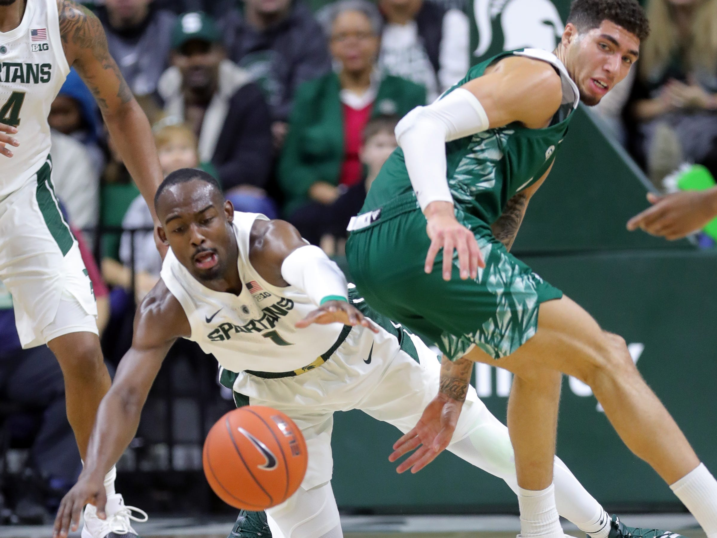 Michigan State guard Joshua Langford dives for the loose ball against Green Bay guard Sandy Cohen III during the first half Sunday, Dec. 16, 2018 at the Breslin Center in East Lansing.