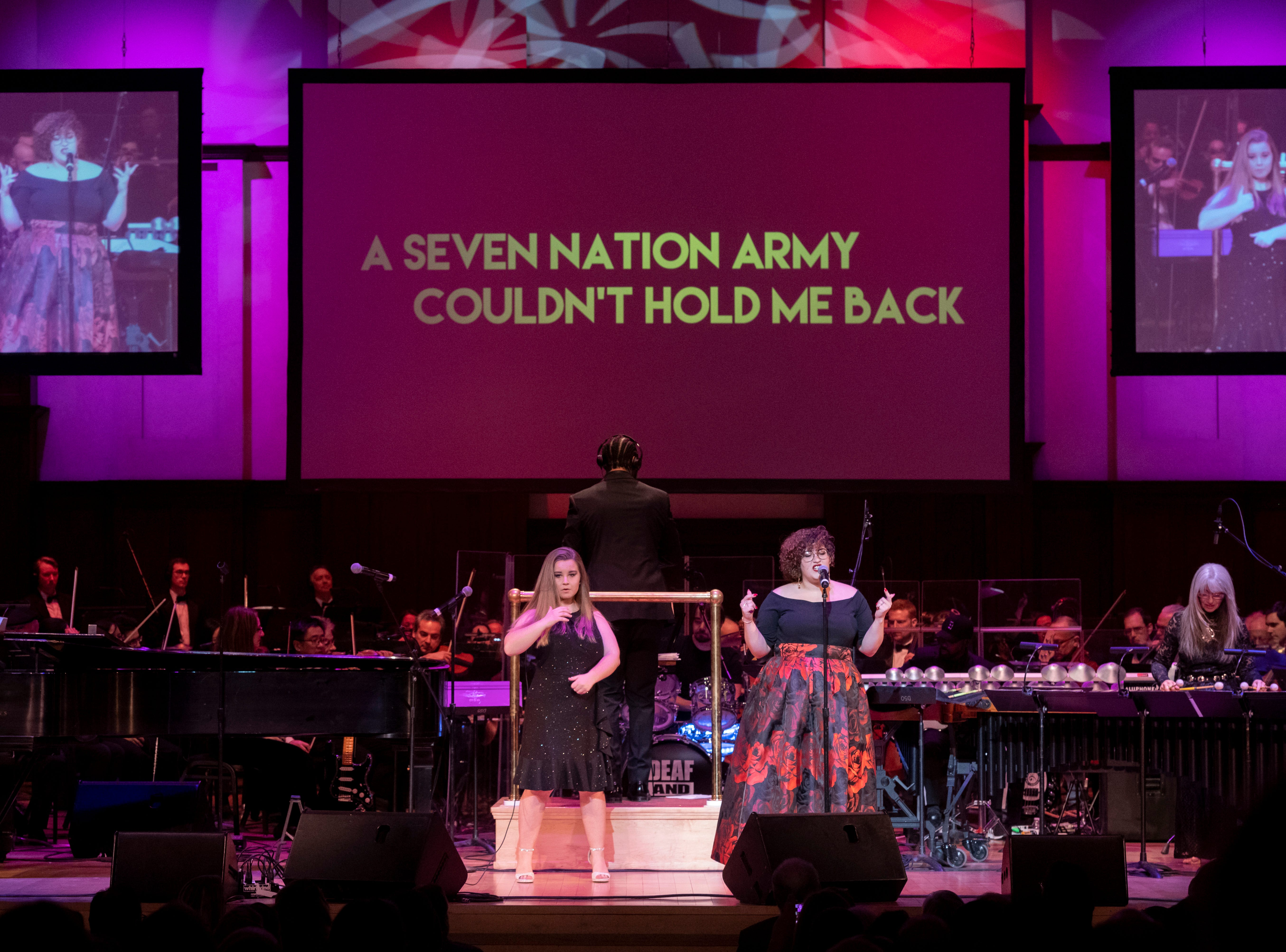 """ASL performer Morgan Nimmo, left, and singer Mama Yaya perform """"Seven Nation Army"""" by the White Stripes during the Deaf and Loud Symphonic Experience at the Detroit Symphony Orchestra, December 16, 2018. Deaf artists and the DSO performed a combination of current and orchestral music in American Sign Language and accompanied by large screen videos with lyrics presented for each song."""