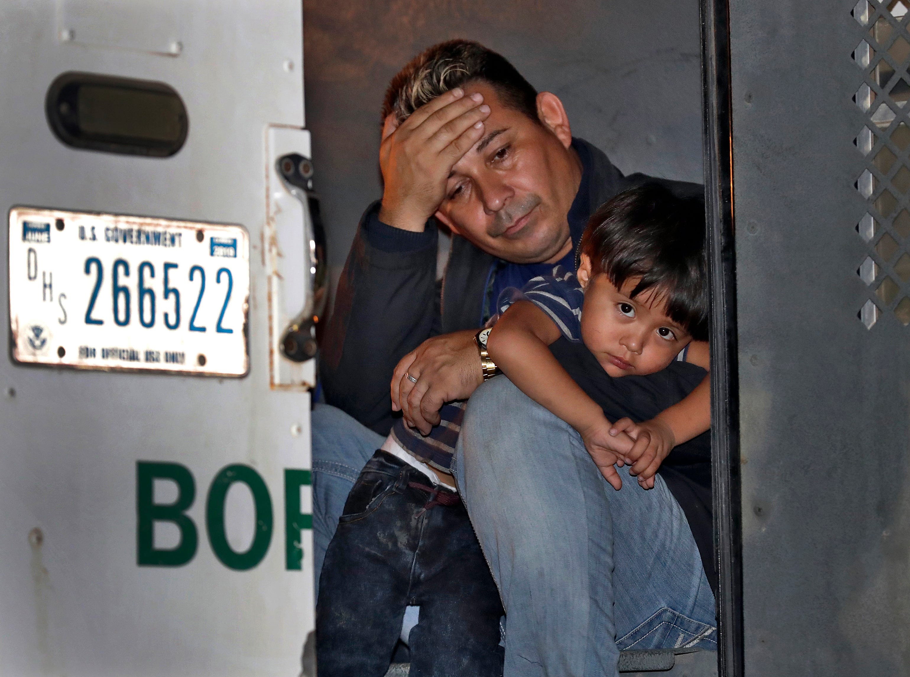 A father and his 3-year-old son are detained in the back of a U.S. Customs and Border Patrol vehicle on July 18, 2018, in San Luis, Ariz. The boy, his father and two siblings were arrested by a U.S. Border Patrol agent who spotted them crossing a canal along the the international border.