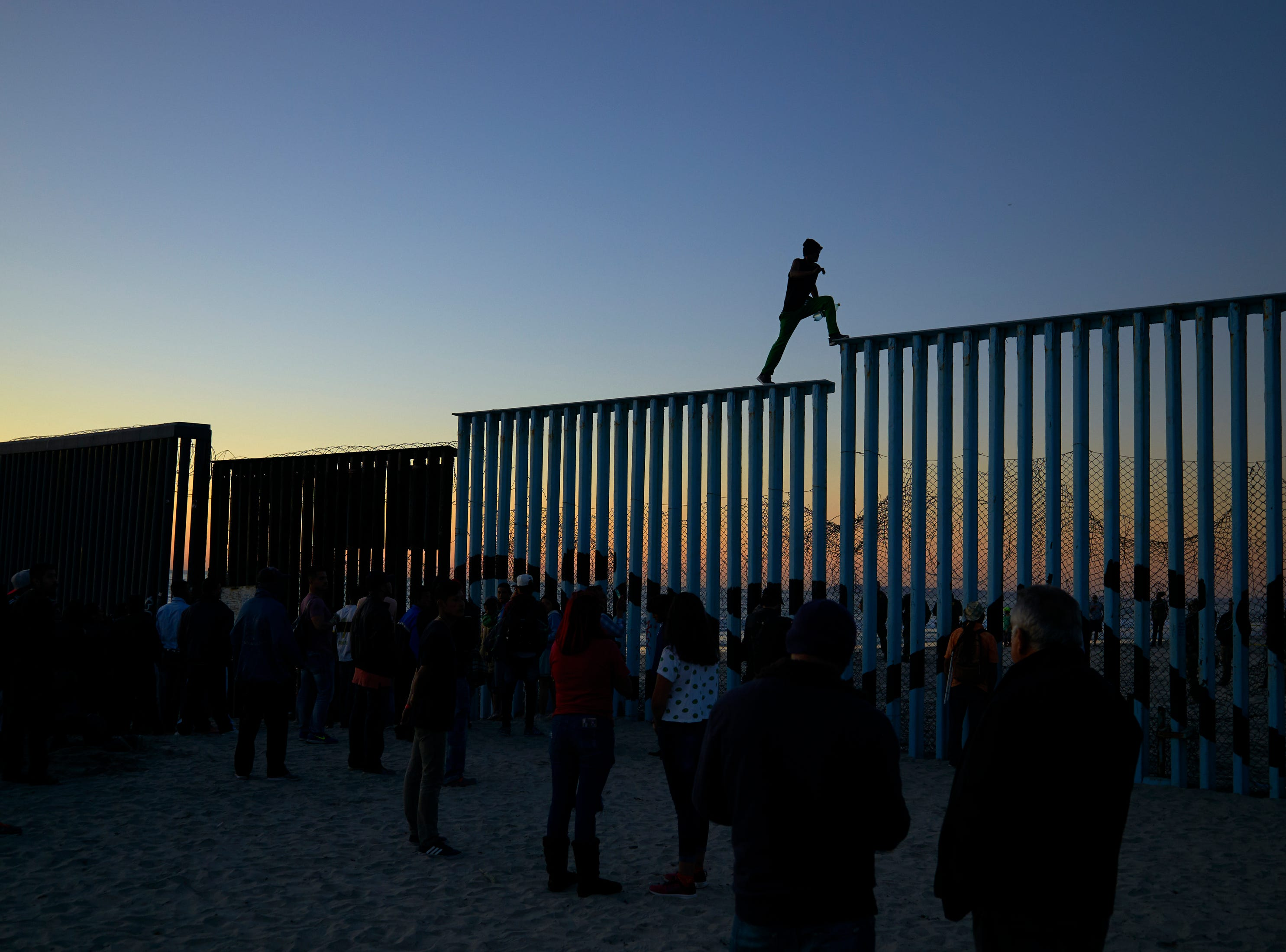 A man from Honduras walks along the top of the border structure separating Mexico and the United States on Nov. 14, 2018, in Tijuana, Mexico.