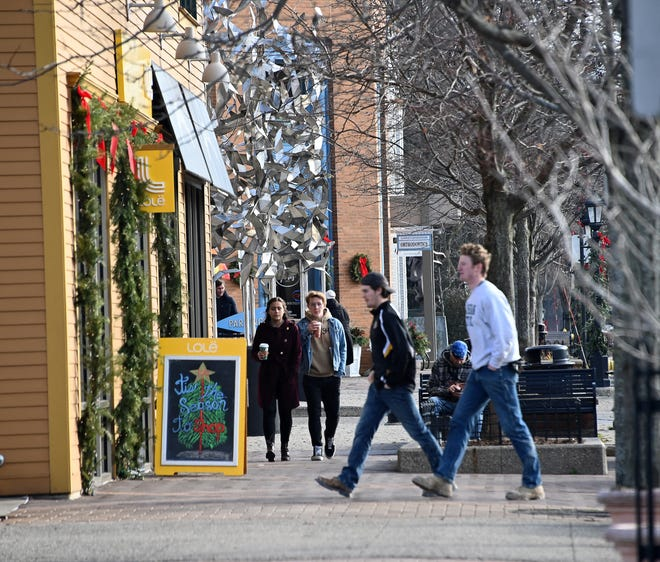 "Young shoppers stroll through the upscale ""Gas Light District"" shopping area in East Grand Rapids. Kent County continues to attract growth in West Michigan."