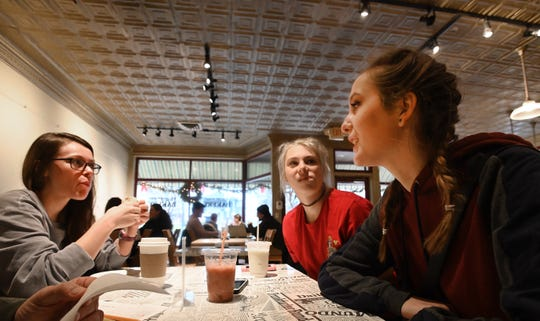 Taylor Davis (right), Katie Johnston (center), and their new roommate, Esther Hansen chat in the Wealthy St. Bakery in 'East Town' Grand Rapids.  The trio met online and were out apartment hunting.
