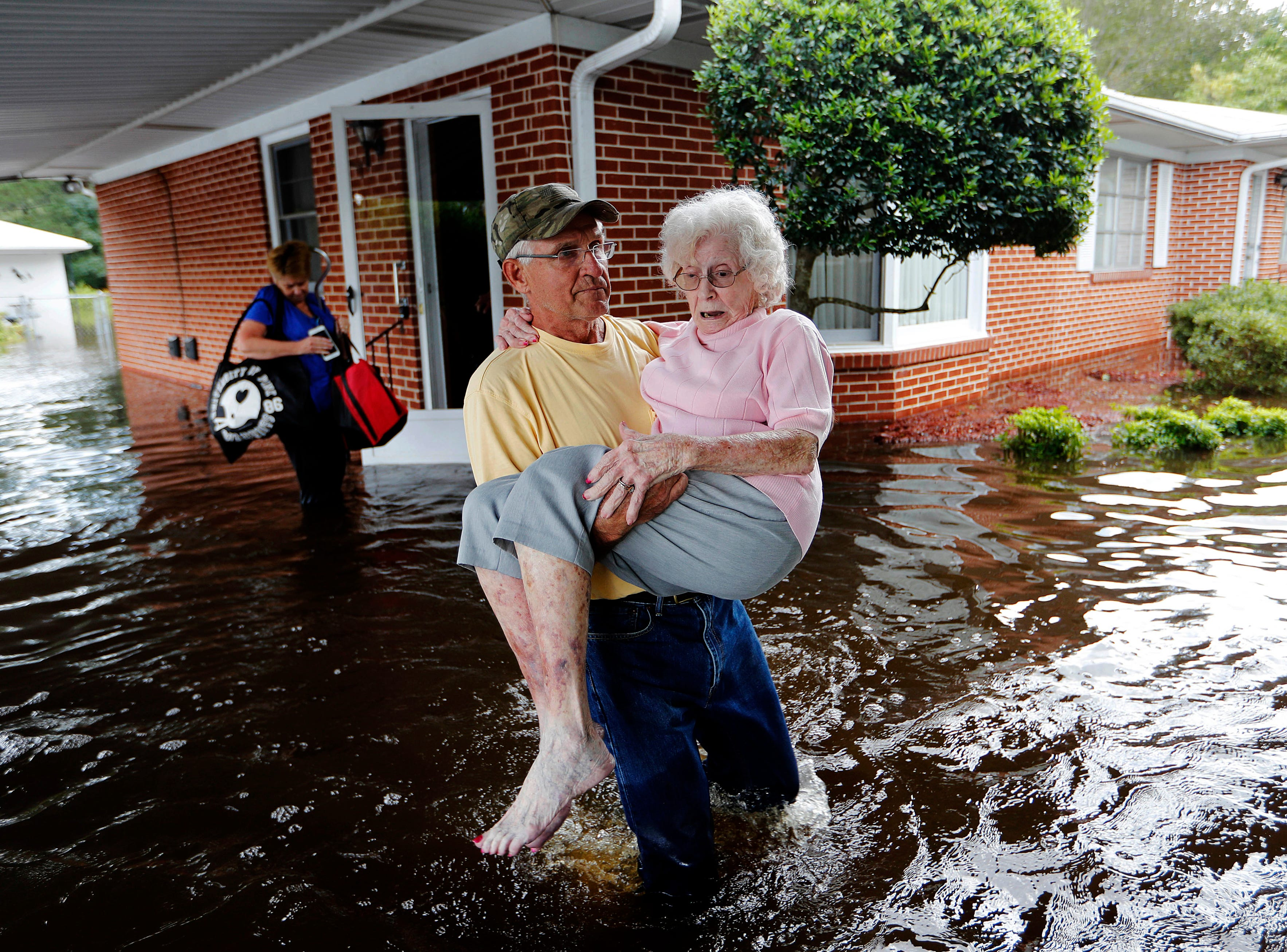 Bob Richling carries Iris Darden, 84, out of her flooded home as her daughter-in-law, Pam Darden, gathers her belongings in the aftermath of Hurricane Florence in Spring Lake, N.C. on Sept. 17, 2018.