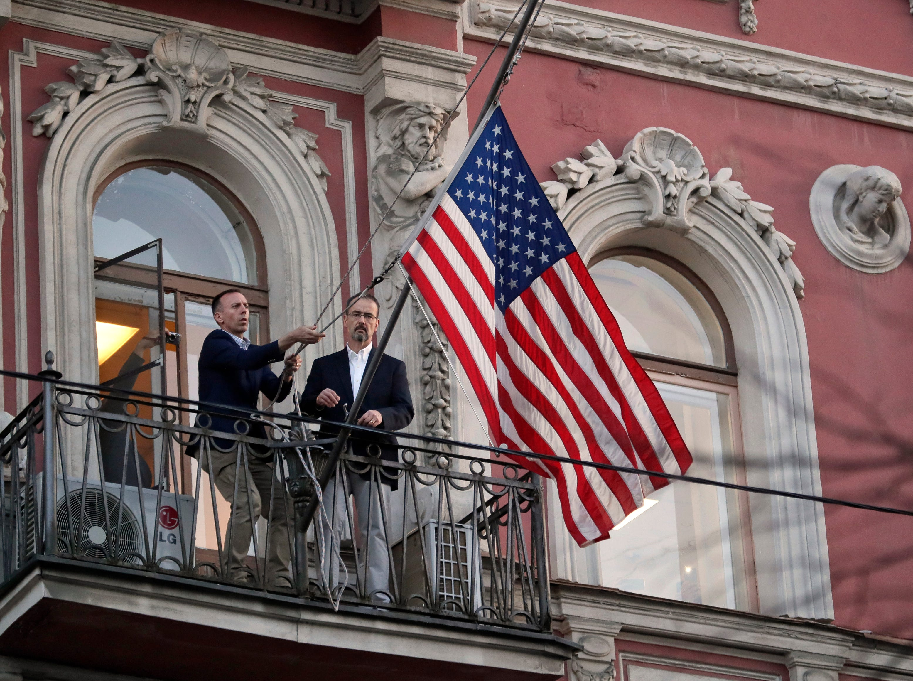 Employees at the U.S. consulate in St. Petersburg, Russia, remove the U.S flag on March 31, 2018, after Russia announced it was closing the consulate and expelling more than 150 diplomats, including 60 Americans. The move was in retaliation for the wave of Western expulsions of Russian diplomats over the poisoning of an ex-spy and his daughter in Britain.
