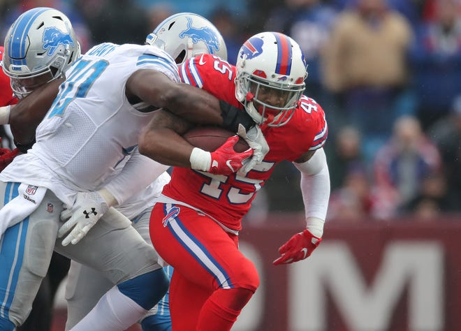 Bills running back Marcus Murphy, right, rushes for a first down in the first quarter as Lions linebacker Jarrad Davis  moves in to bring him down on Sunday.