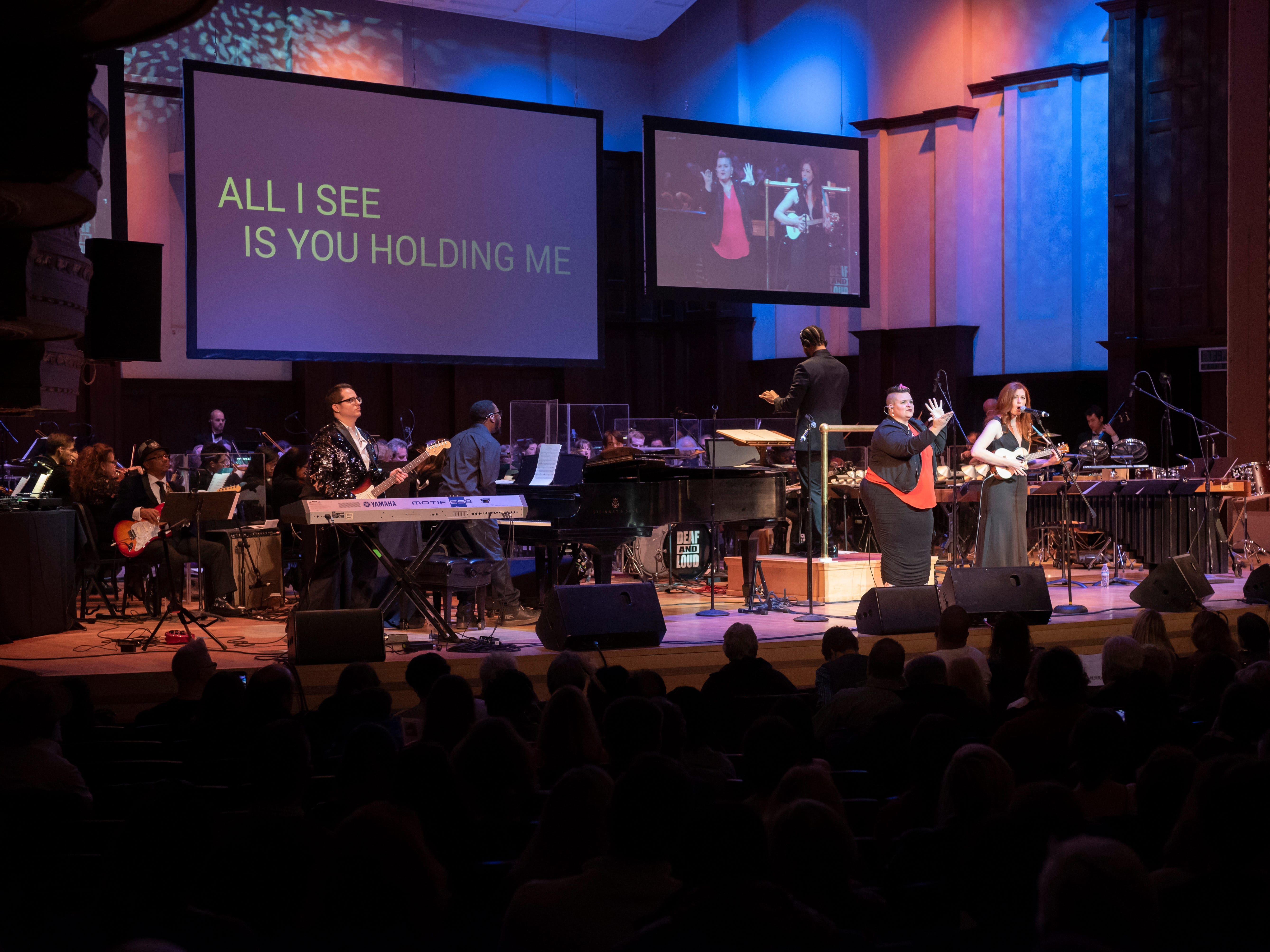 ASL performer Amber Galloway Gallego, left, and musician Mandy Harvey perform during the Deaf and Loud Symphonic Experience at the Detroit Symphony Orchestra, December 16, 2018. Deaf artists and the DSO performed a combination of contemporary and orchestral music in American Sign Language with lyrics projected for each song.
