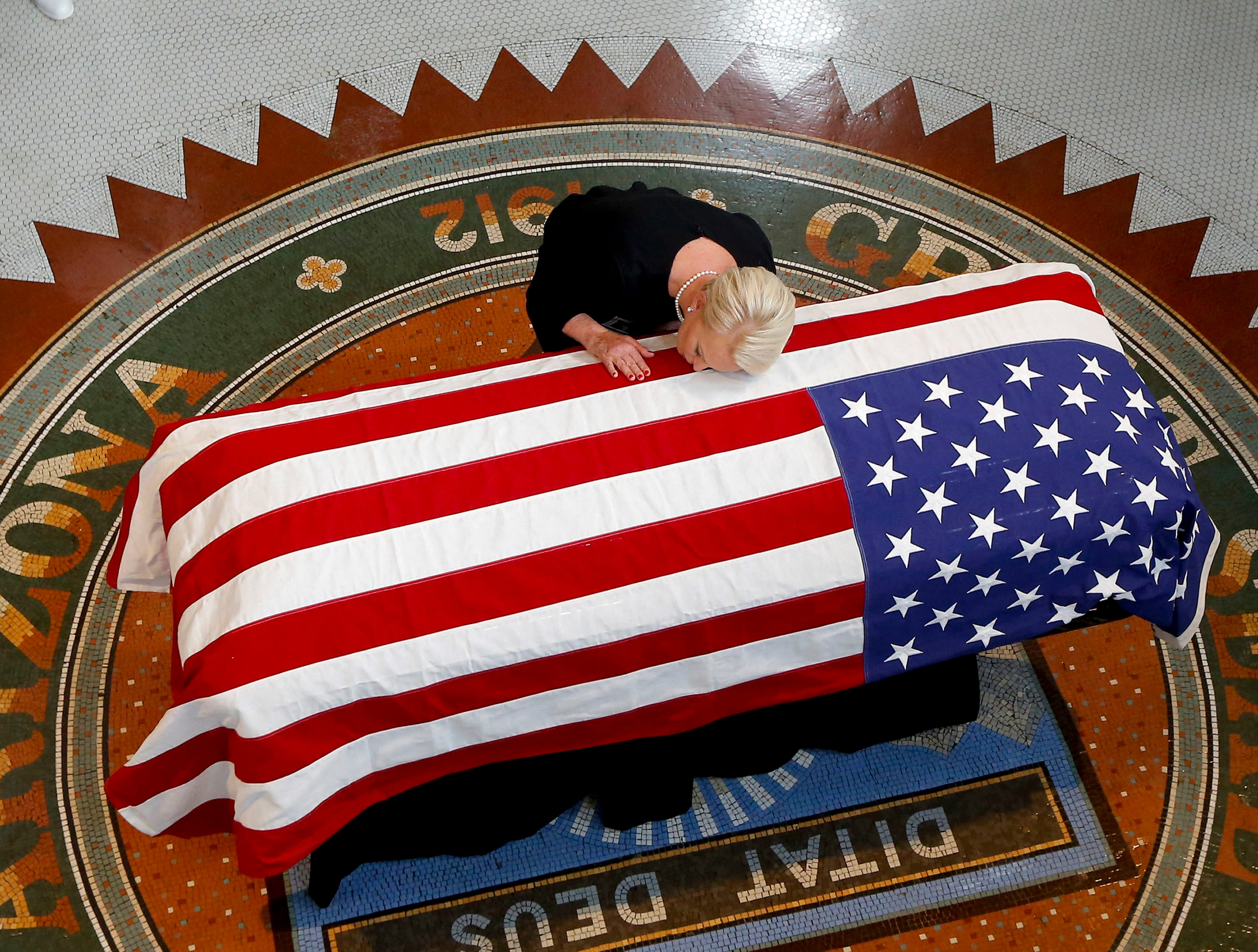 Cindy McCain, wife of Sen. John McCain, R-Ariz., rests her head on his casket during a memorial service at the Arizona Capitol in Phoenix on Aug. 29, 2018.