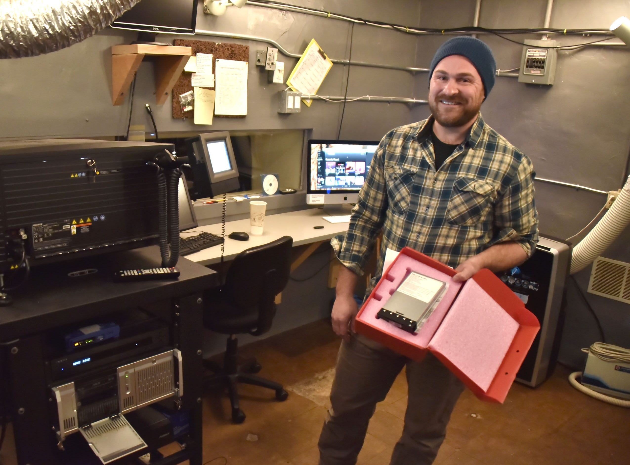 Erik Bahle, manager of the 200-seat Bay theater in Suttons Bay, Michigan holds a digital hard drive which contains a movie, replacing the old 35-mm film that was used to show movies.
