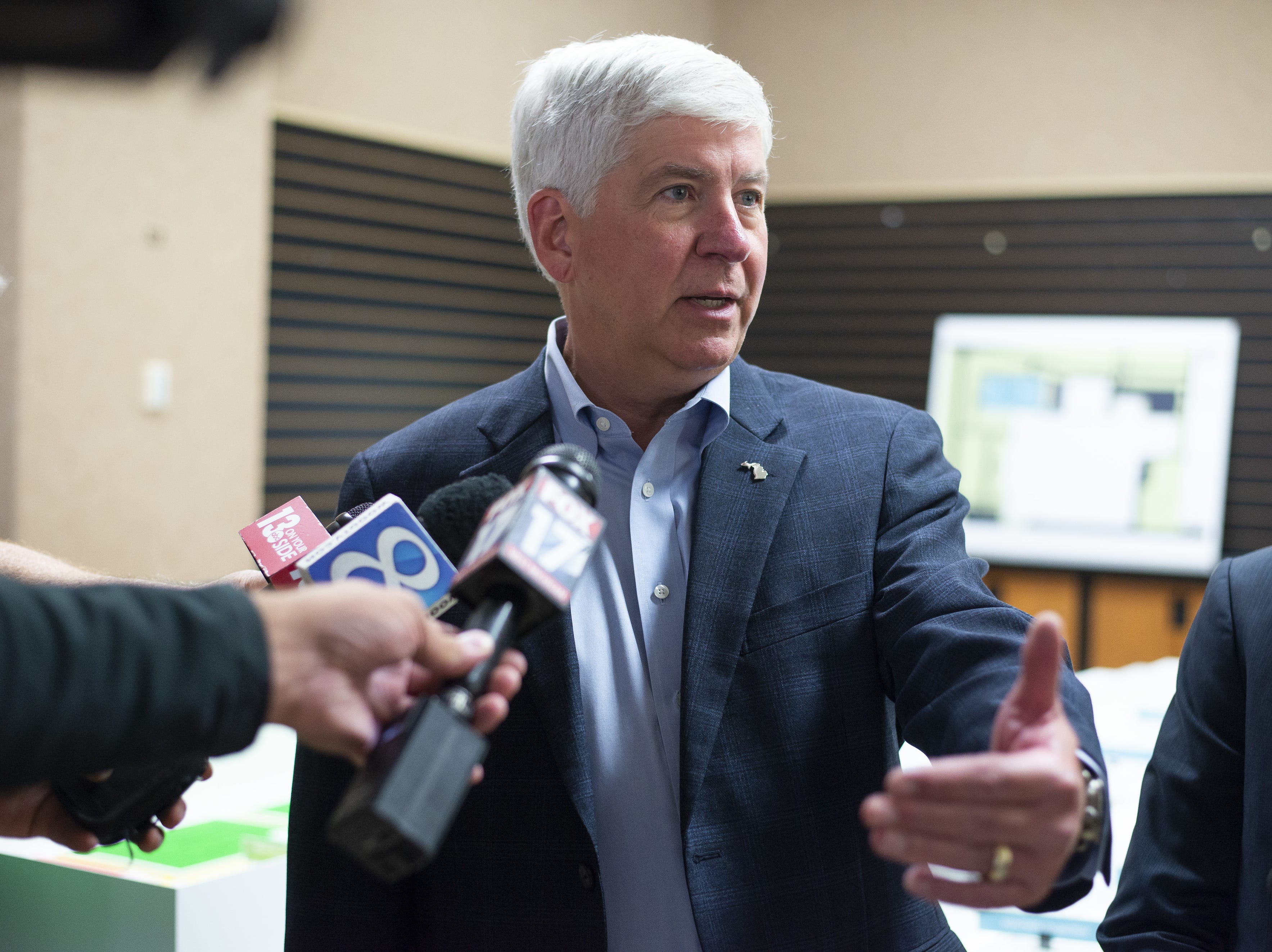 FILE - In this July 24, 2018 file photo, Gov. Rick Snyder answers questions after a press conference in Portage, Mich. Snyder has signed Republican-backed laws to significantly scale back citizen-initiated measures to raise the minimum wage and require paid sick leave for workers. The term-limited Republican governor's move Friday, Dec. 14, 2018, is sure to prompt a lawsuit over an unprecedented strategy adopted by lame-duck lawmakers. (Daniel Vasta/Kalamazoo Gazette via AP File)