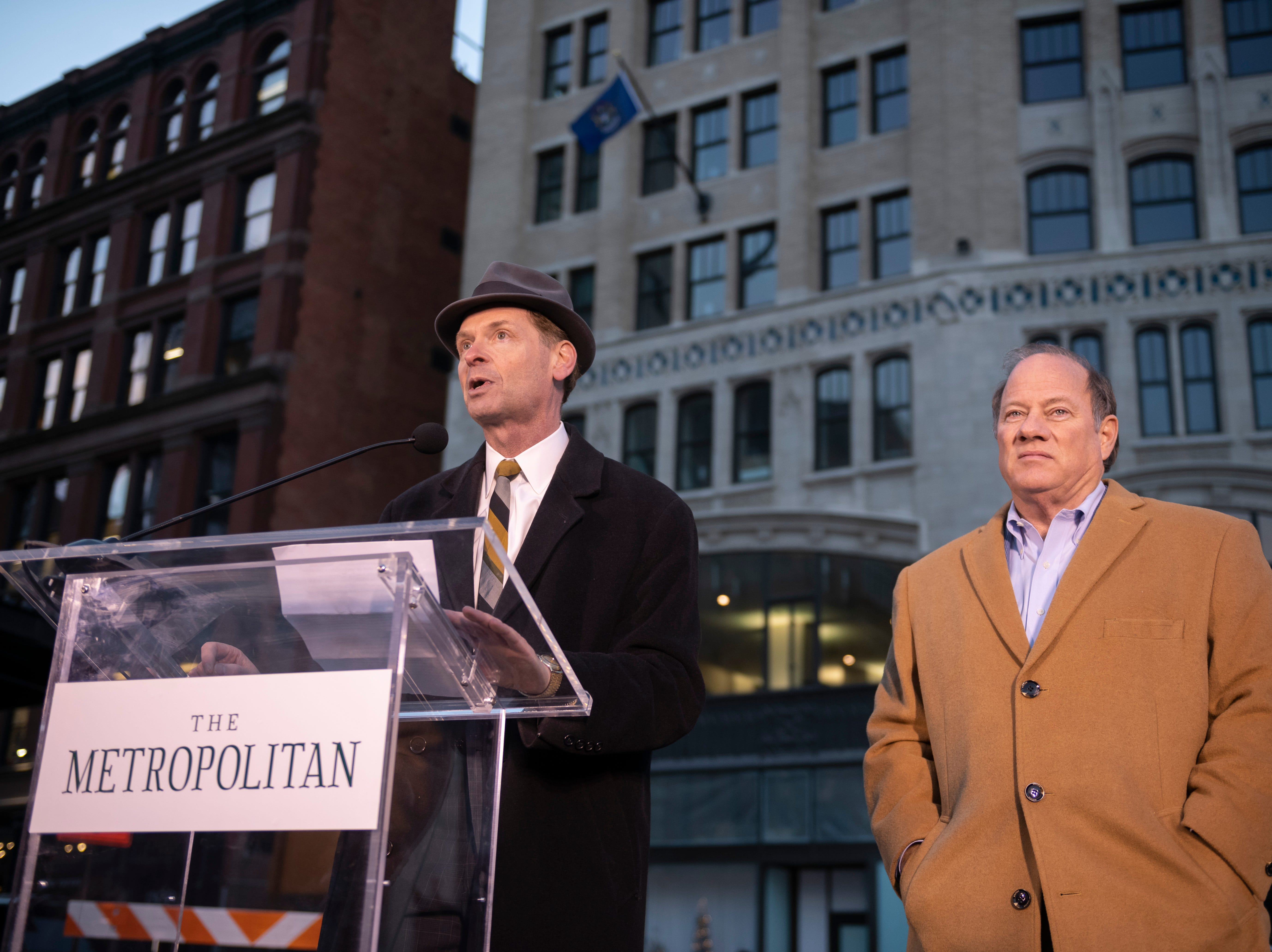 David Di Rita, principal of the Roxbury Group, left, and Detroit Mayor Mike Duggan stand on stage during a public dedication celebration of the Metropolitan building.